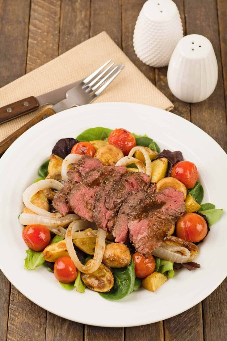 This tasty combination of grilled sirloin, baby potatoes, cherry tomatoes and mushrooms is served over mixed greens to make a hearty main dish salad. #steaksalad #dinnersalad #maindishsalad