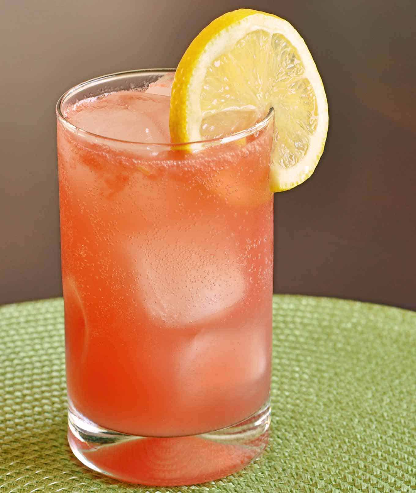 Collins glass filled with muddled fresh watermelon, vodka limoncello, lemon juice, and soda garnished with a lemon wheel.