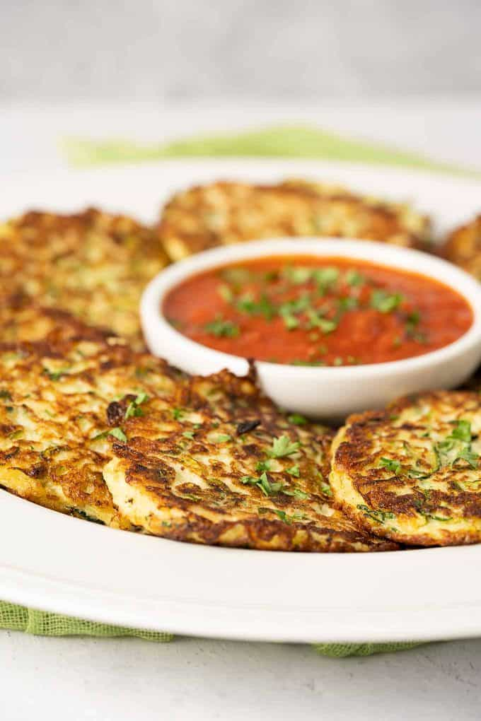 Platter of zucchini fritters with small bowl of marinara dipping sauce