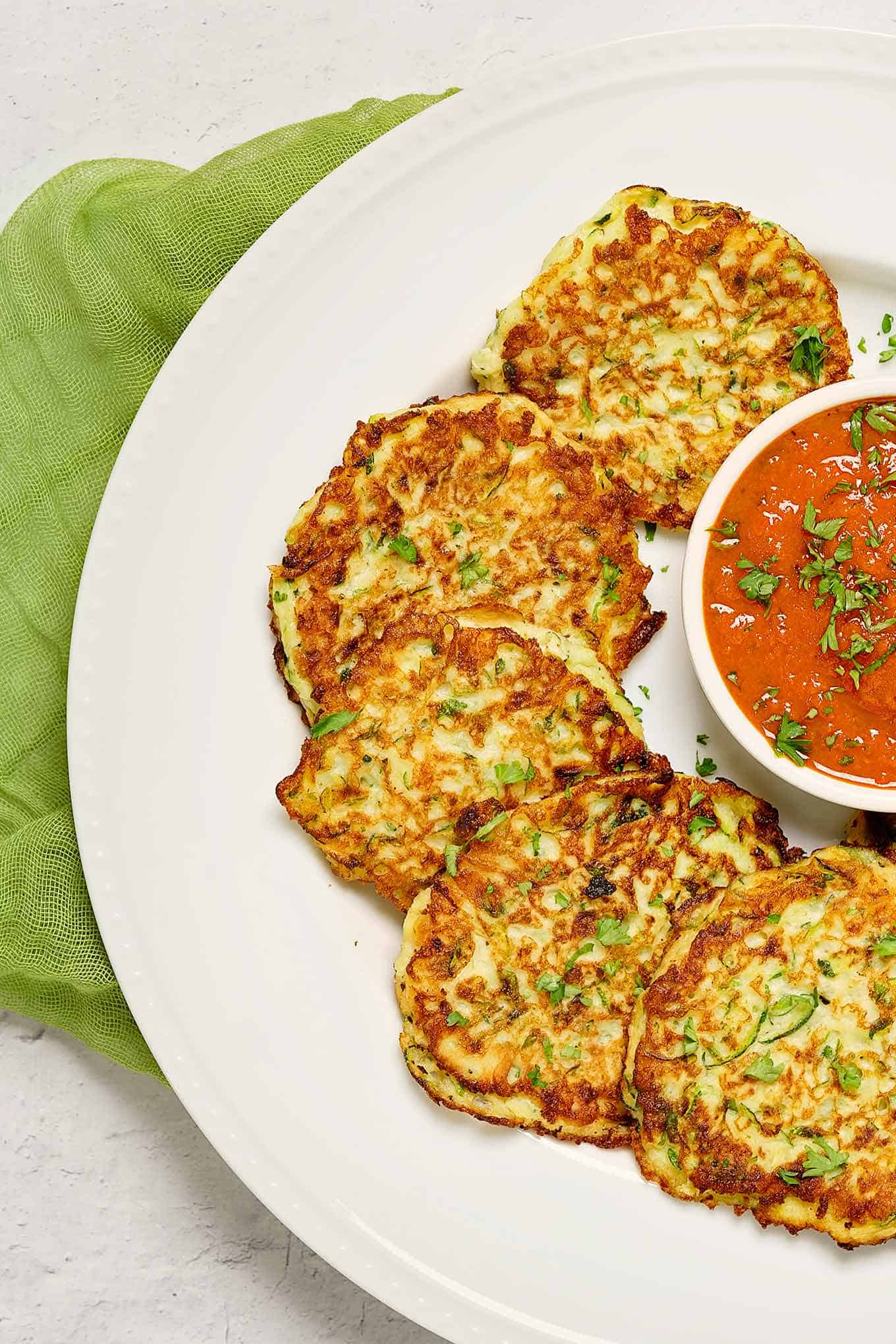 Zucchini fritters arranged on a serving plate with a bowl of marinara sauce for dipping in the center.